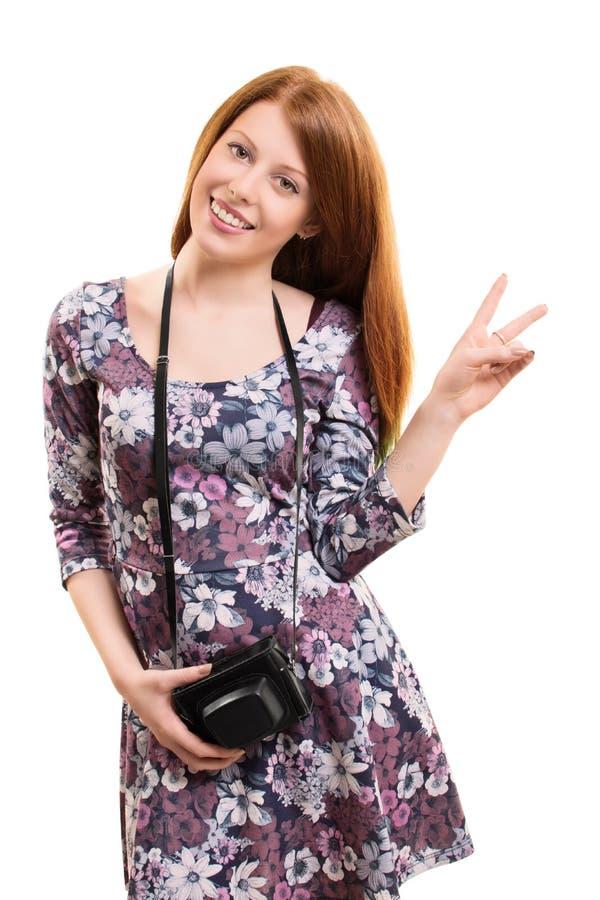 Schönes junges Mädchen, das eine Weinlesekamera lächelt und hält stockfoto