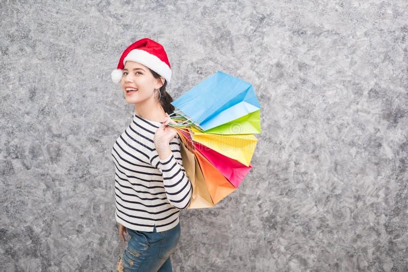 Schönes junges Mädchen, das einen Sankt-Hut hält viele Einkaufstaschen trägt stockbilder