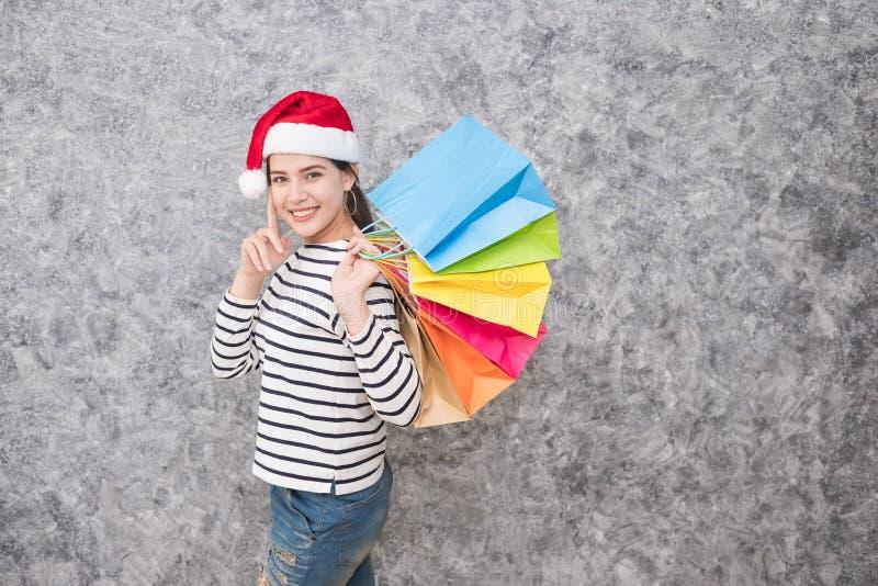 Schönes junges Mädchen, das einen Sankt-Hut hält viele Einkaufstaschen trägt lizenzfreies stockbild