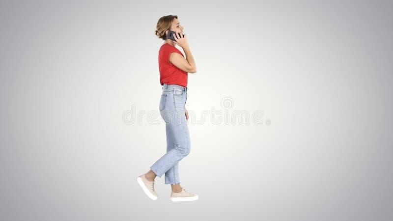 Schönes junges Mädchen, das einen Telefonanruf geht auf Steigungshintergrund hat stockfoto