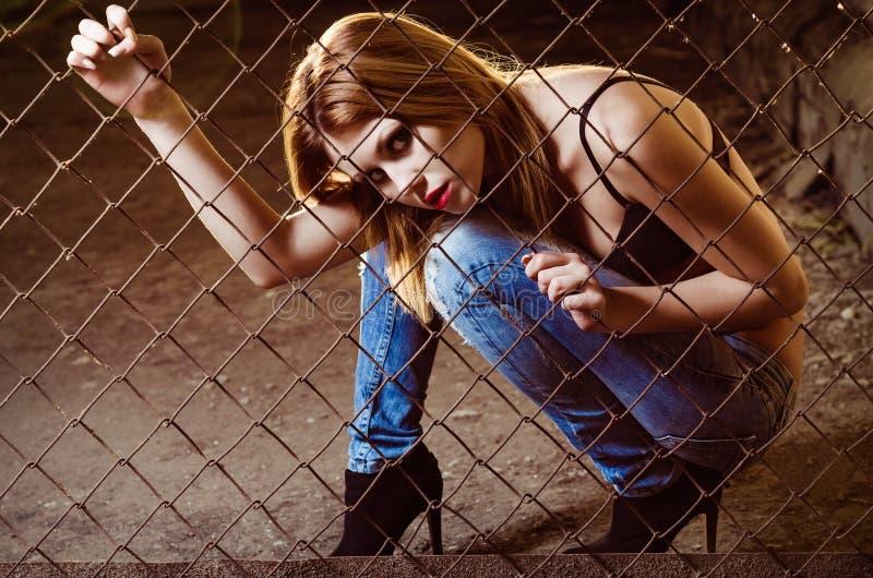 Schönes junges Mädchen, das hinter metallischem Gitter sitzt lizenzfreie stockfotos