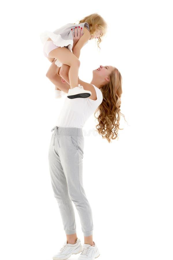 Schönes junges Mädchen, das ihre kleine Schwester in ihren Armen hält lizenzfreie stockfotos
