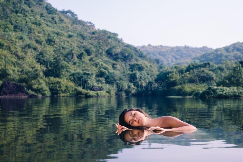 Schönes junges Mädchen, das im Wasserspiegel auf einem Hintergrund von grünen Hügeln sich entspannt stockfotografie