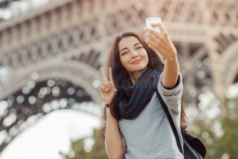Schönes junges Mädchen, das lustiges selfie mit ihrem Handy nahe dem Eiffelturm nimmt stockfotos