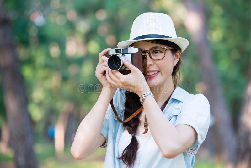 Schönes junges Mädchen, das mit der Retro- fotografierenden Kamera, ou lächelt lizenzfreie stockfotos