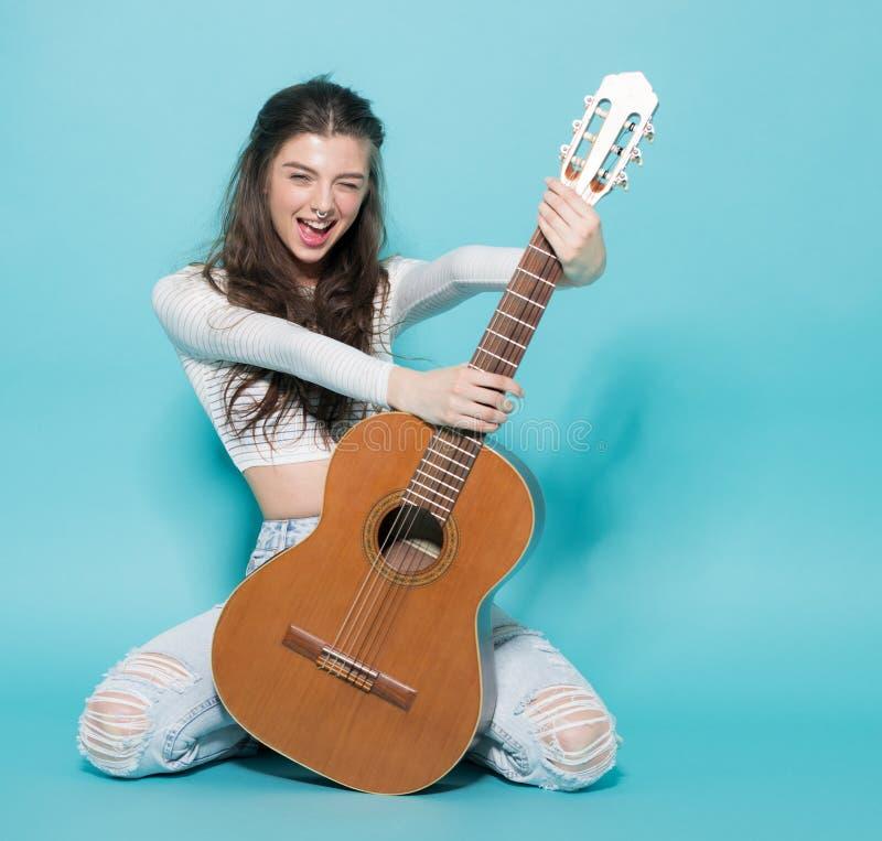 Schönes junges Mädchen, das mit Gitarre aufwirft lizenzfreies stockbild