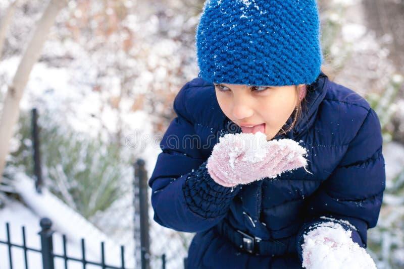 Schönes junges Mädchen, das mit Schnee im Park spielt lizenzfreies stockbild
