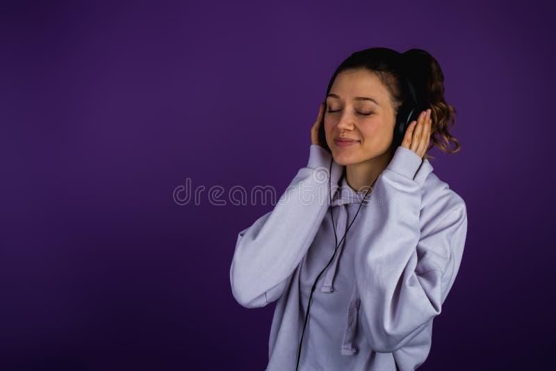 Schönes junges Mädchen, das Musik in den Kopfhörern in einem Sweatshirt auf einem purpurroten Hintergrund hört stockbilder