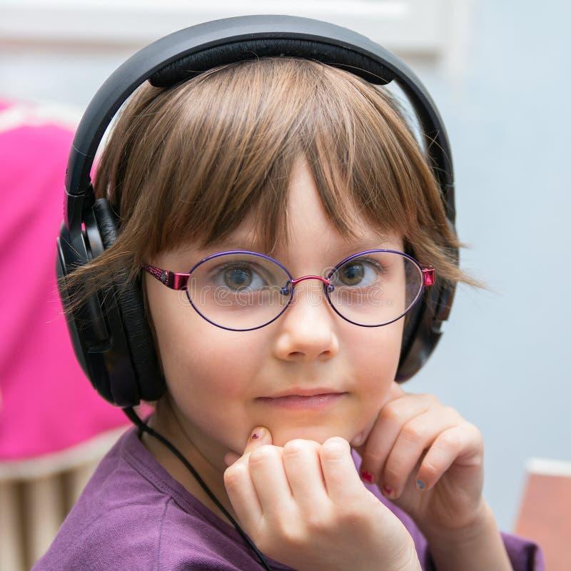 Schönes junges Mädchen, das Musik mit Kopfhörer hört stockbilder