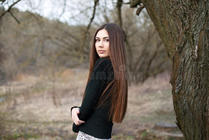 Schönes junges Mädchen, das nahe einem Baum im Garten backgrou steht lizenzfreie stockfotos
