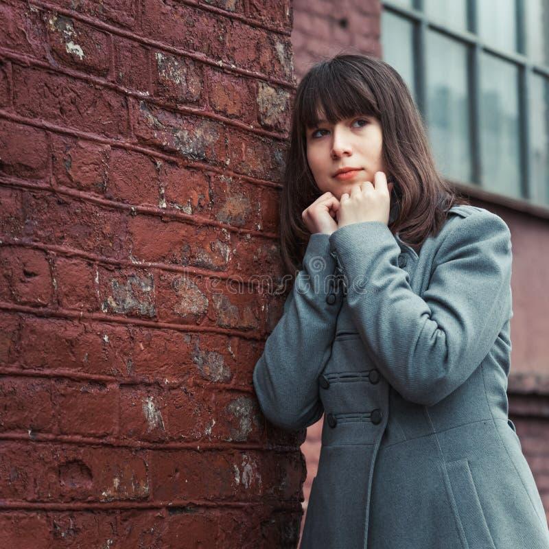 Schönes junges Mädchen, das nahe einer Backsteinmauer steht stockfotos