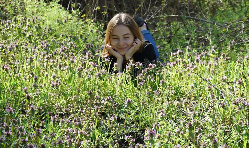 Schönes junges Mädchen, das am Rand des Waldes, lebend mit Natur liegt stockbild