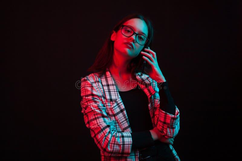 Schönes junges Mädchen, das am Telefon spricht und die Kamera im Studio mit bunter Beleuchtung betrachtet lizenzfreies stockfoto
