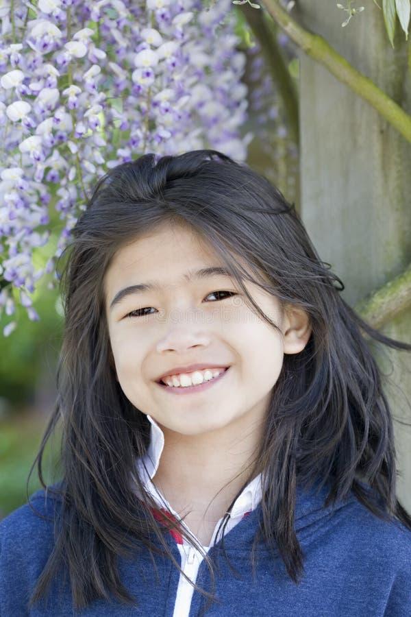 Schönes junges Mädchen, das unter Glyziniereben steht lizenzfreies stockbild