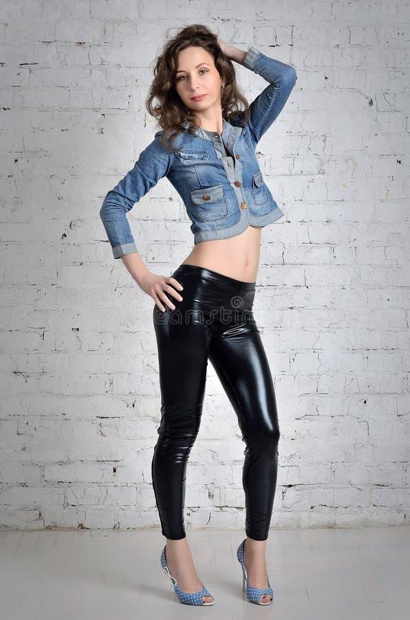 Schönes junges Mädchen, das zum Willen der Wand aufwirft lizenzfreie stockfotografie