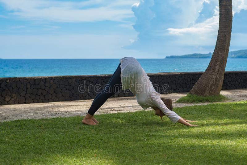 Schönes junges Mädchen in den Gamaschen und im Kittel macht Yogapraxis, die Meditation und dehnt asana auf dem Ozeanstrand Bali I lizenzfreies stockfoto