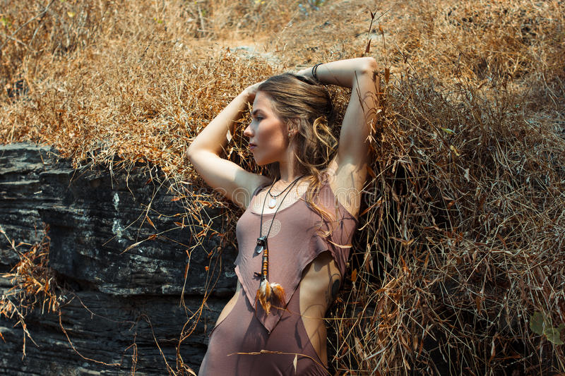 Schönes junges Mädchen in der fantastischen Kleidung unter trockenem Gras und dem Felsen stockfotos
