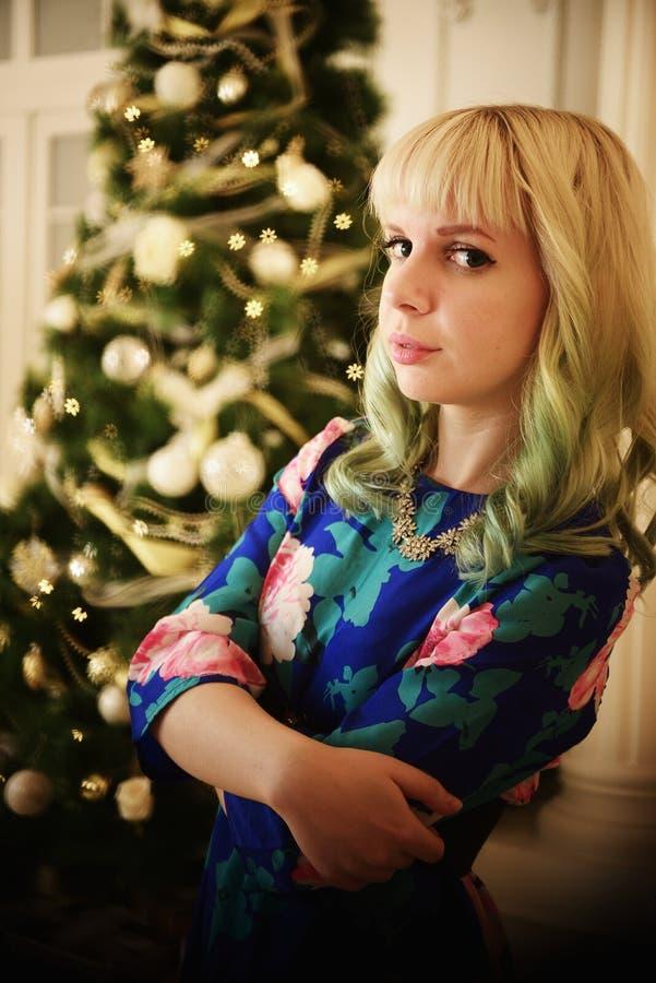 Schönes junges Mädchen des Porträts nahe Weihnachtsbaum mit Geschenken lizenzfreie stockbilder