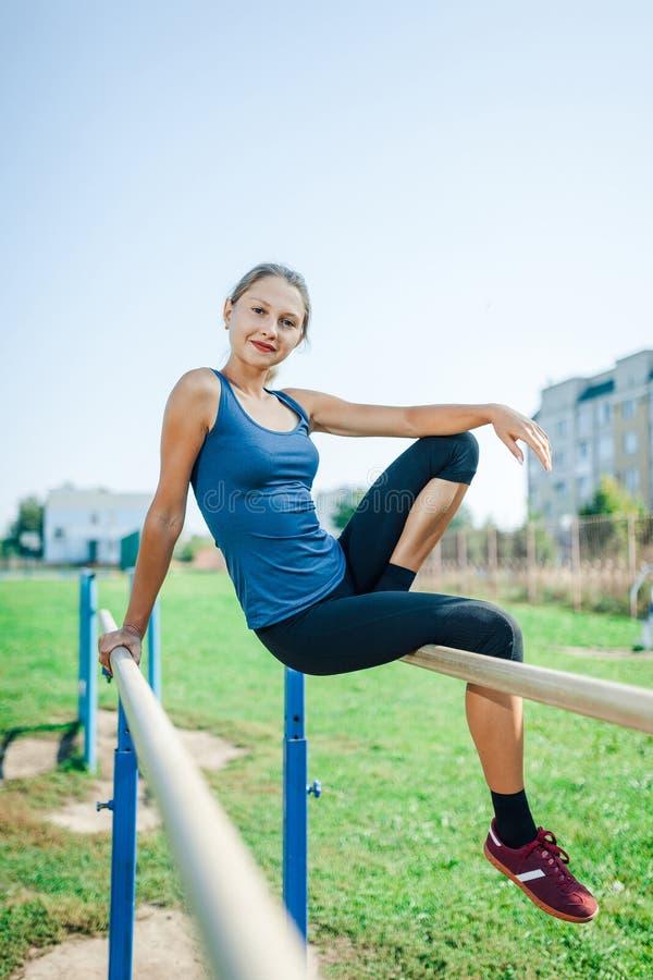 Schönes junges Mädchen in einem blauen Hemd und in Gamaschen, die auf dem Stufenbarren, auf dem Sportplatz im Freien im Sommer be lizenzfreies stockbild