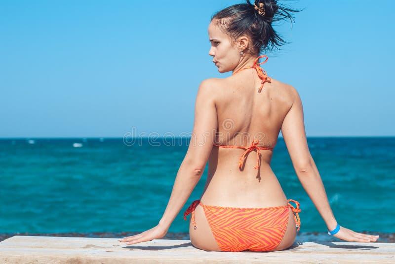 Schönes junges Mädchen in einem gestreiften orange Badeanzug sitzt mit ihr zurück zu uns auf der Bank über Hintergrund des blauen lizenzfreies stockbild