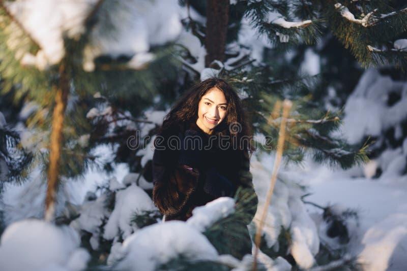 Schönes junges Mädchen in einem schneebedeckten Wald lizenzfreie stockbilder