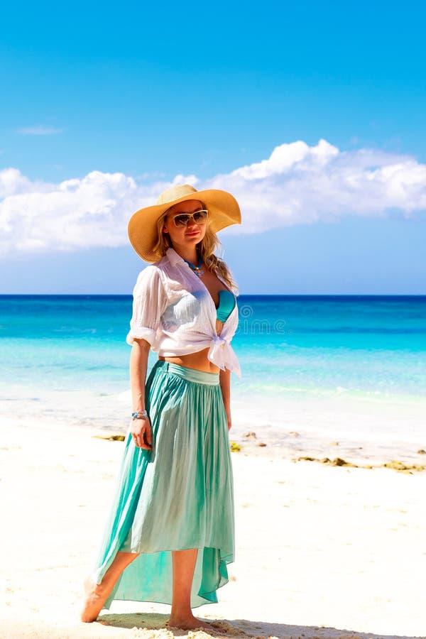 Schönes junges Mädchen in einem Strohhut auf einem tropischen Strand stockfotografie