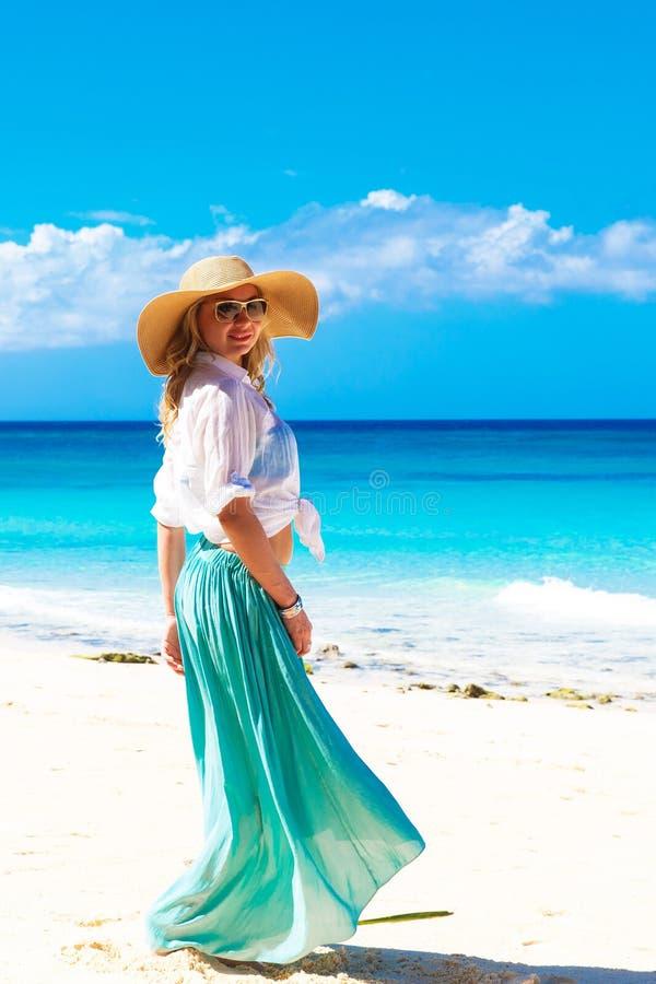 Schönes junges Mädchen in einem Strohhut auf einem tropischen Strand lizenzfreie stockbilder