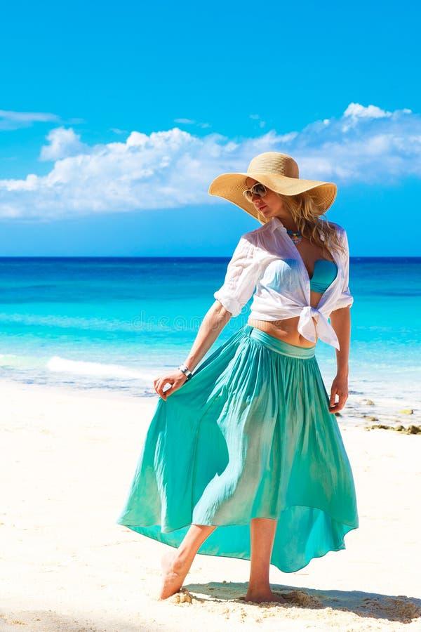 Schönes junges Mädchen in einem Strohhut auf einem tropischen Strand stockfoto