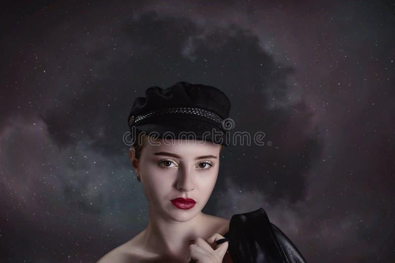 Schönes junges Mädchen in einer schwarzen Kappe und in einer Lederjacke im ha lizenzfreie stockfotos