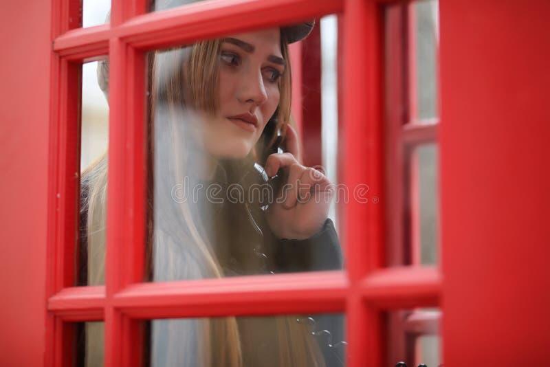 Schönes junges Mädchen in einer Telefonzelle Das Mädchen spricht auf Th lizenzfreies stockfoto