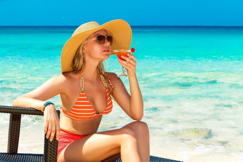 Schönes junges Mädchen im Bikini sitzt auf einer Sonnenruhesesselküste lizenzfreie stockbilder