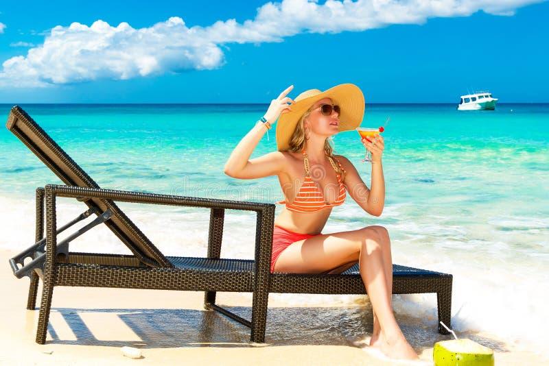 Schönes junges Mädchen im Bikini sitzt auf einer Sonnenruhesesselküste lizenzfreie stockfotografie