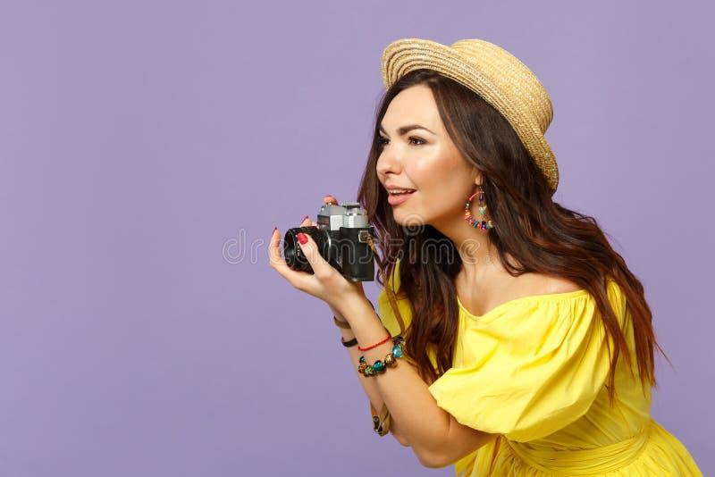 Schönes junges Mädchen im gelben Zylinder, der Foto auf der Retro- Weinlesefotokamera schaut beiseite lokalisiert auf Pastell mac lizenzfreie stockfotografie