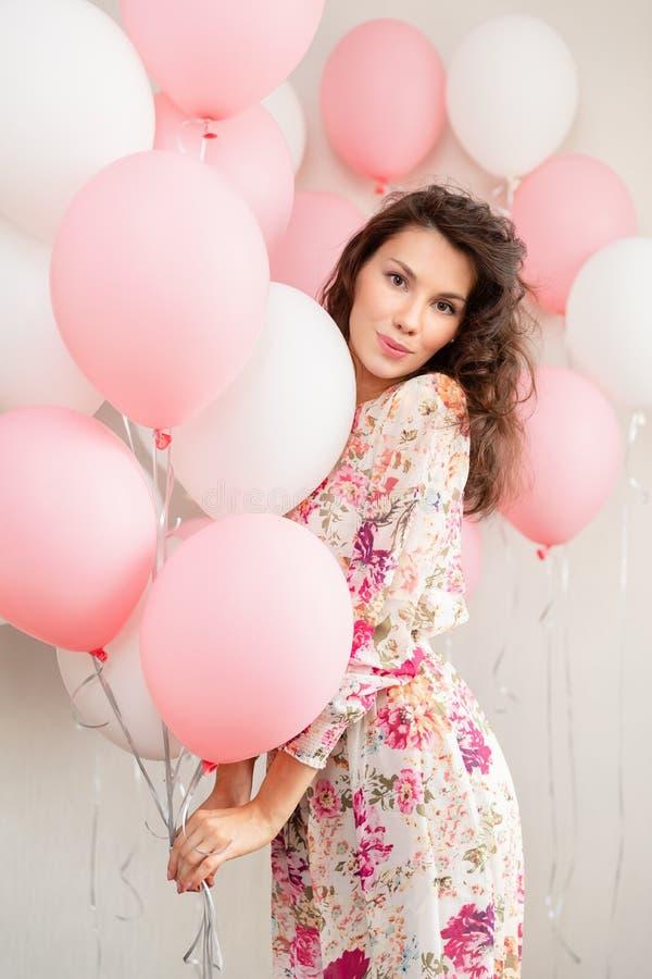 Schönes junges Mädchen im Kleid mit Ballonen auf Geburtstag Porträt der netten Frau mit mehrfarbigem Ballon Netter Brunette stockbilder