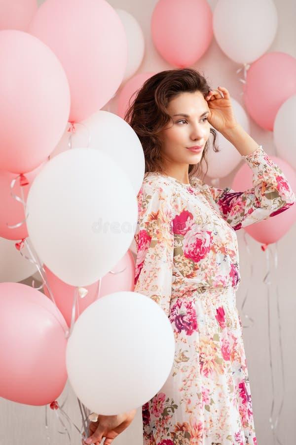 Schönes junges Mädchen im Kleid mit Ballonen auf Geburtstag Porträt der netten Frau mit mehrfarbigem Ballon Netter Brunette stockfoto