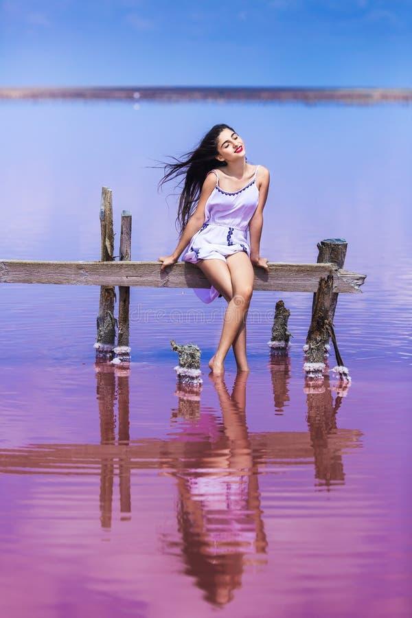 Schönes junges Mädchen im langen weißen Kleid, das auf salzigem rosa See aufwirft stockfotografie