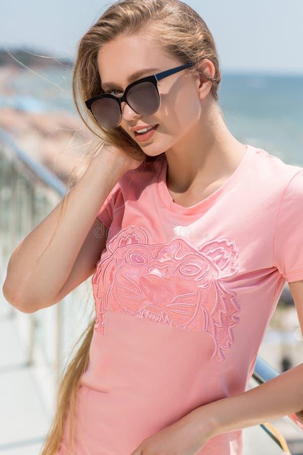 Schönes junges Mädchen im rosa Kleid und mit dem blonden Haar Reizend Mode-Modell-Frau in den Sonnenbrillen mit einem netten Läch lizenzfreies stockfoto