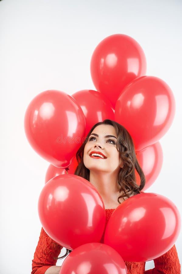 Schönes junges Mädchen im roten Kleid auf Feier stockfoto