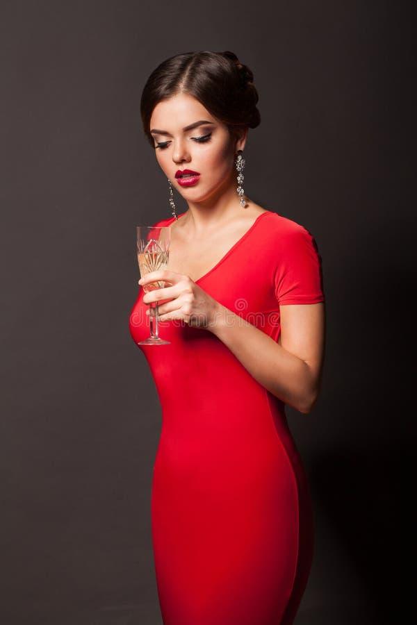 Schönes junges Mädchen im roten Kleid, das mit Glas Champagner steht stockbilder