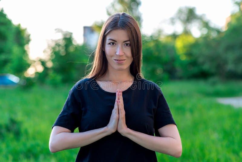 Schönes junges Mädchen im Sommer im Park im Urlaub Eine Geste zeigt Gebet mit seinen Händen Glückliches Lächeln Er schaut stockbilder