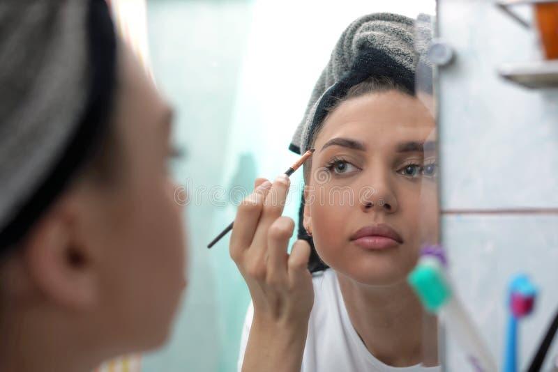 Schönes junges Mädchen malt vor dem Spiegel nach einer Dusche, Morgenmake-up lizenzfreies stockbild