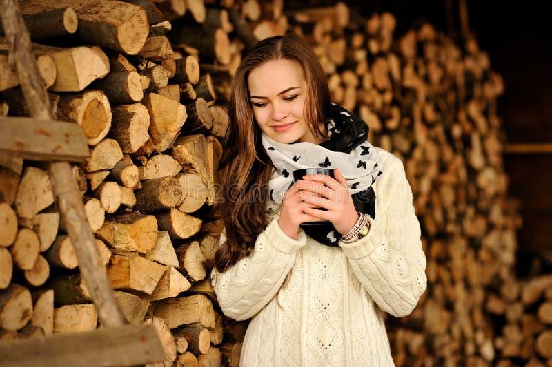 Schönes junges Mädchen mit Cup des warmen Getränks in der kalten Jahreszeit lizenzfreie stockfotos