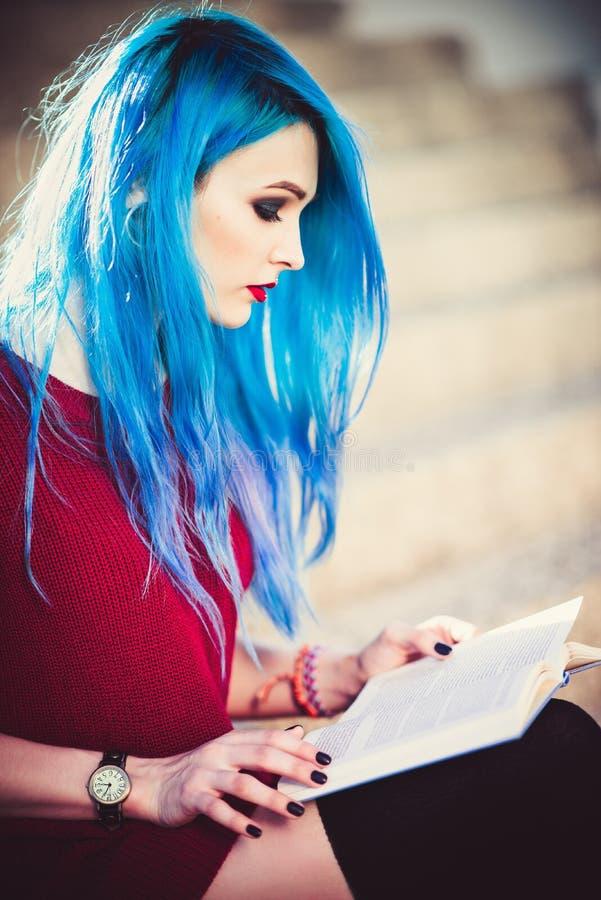 Schönes junges Mädchen mit dem blauen Haar, das auf Treppe sitzt und ein Buch liest nahaufnahme lizenzfreie stockfotos