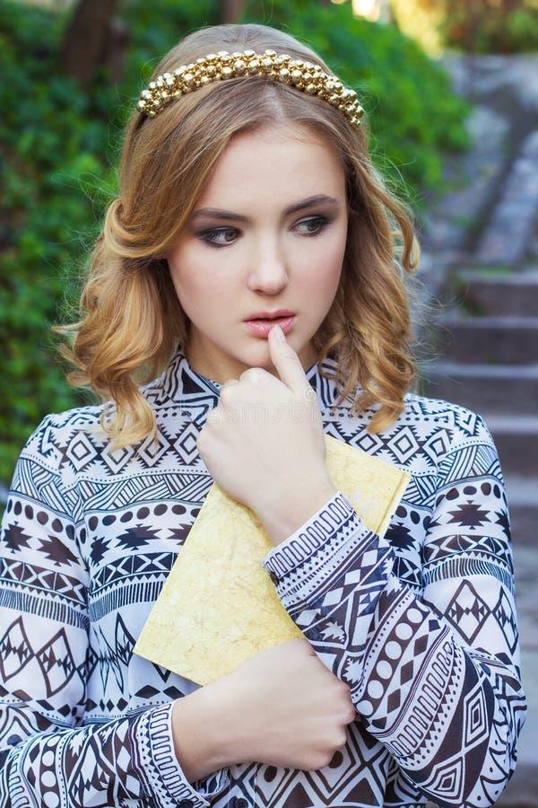 Schönes junges Mädchen mit dem blonden Haar und blauen den Augen, die ein Buch in seinen Händen halten stockbilder