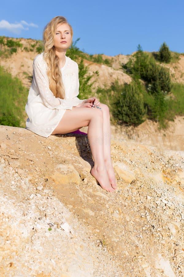 Schönes junges Mädchen mit dem langen blonden Haar in einem weißen Kleid, das auf dem Strand, der See an einem hellen sonnigen Ta stockbild