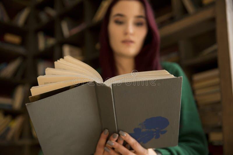 Schönes junges Mädchen mit dem langen Haar liest ein Buch in der Bibliothek stockfotos