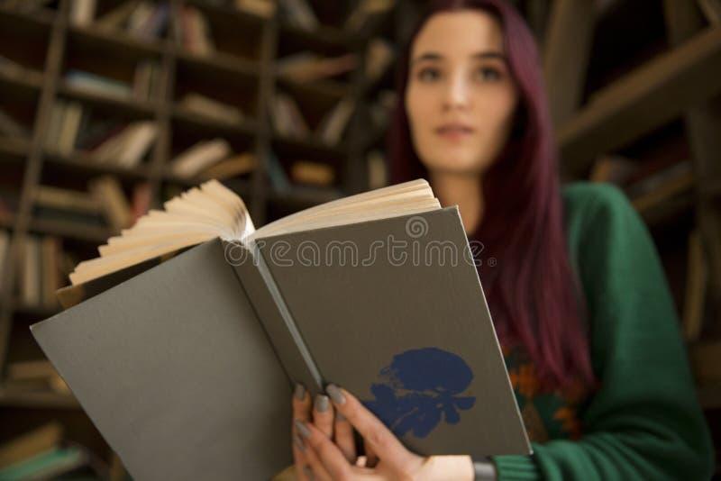 Schönes junges Mädchen mit dem langen Haar liest ein Buch in der Bibliothek lizenzfreies stockbild