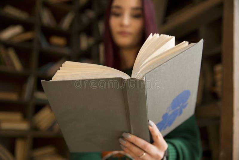 Schönes junges Mädchen mit dem langen Haar liest ein Buch in der Bibliothek lizenzfreie stockbilder
