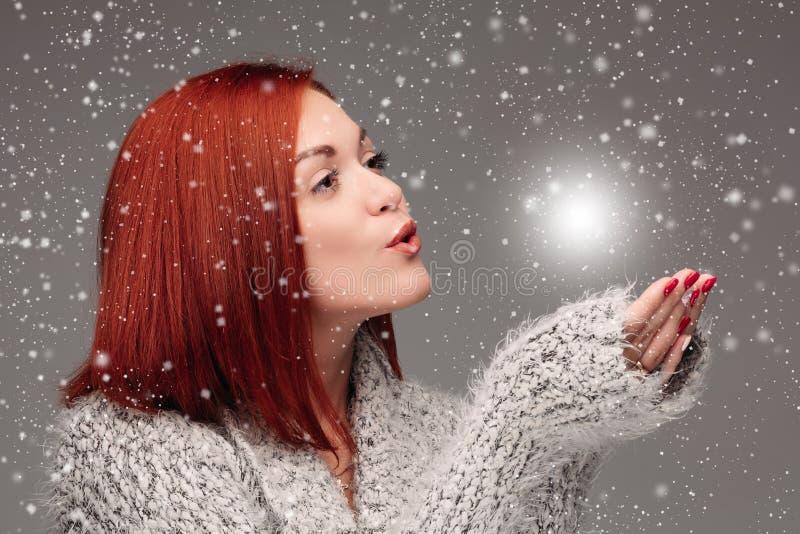 Schönes junges Mädchen mit dem roten Haar und roten den Nägeln, die ihre Hände zusammenhalten und auf weißem erleichterndem Ball  stockfoto