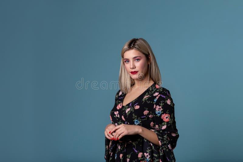 Schönes junges Mädchen mit den hellen Lippen und blonden dem Haar, die im Studio aufwirft lizenzfreie stockfotografie